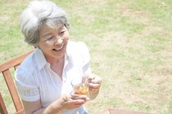 A senior Japanese woman laughs as she takes tea in the garden