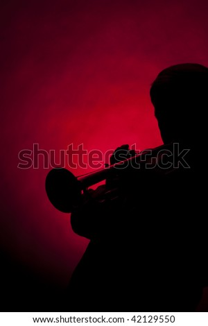 A senior male man trumpet player performer in silhouette isolated against a spotlight red background.