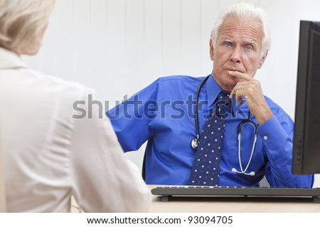 A senior male medical doctor looking thoughtful with a female patient and computer at his desk in an office at a hospital