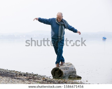 A senior man balancing on a log at the edge of a lake
