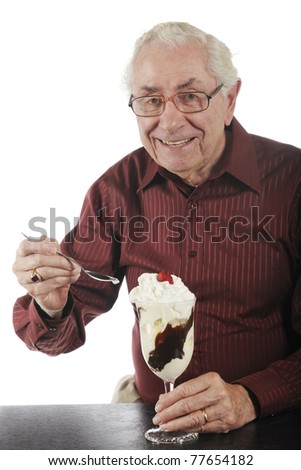 A senior man delighted with his large, hot fudge sundae.  Isolated on white.