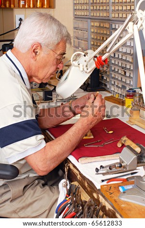 A senior man doing intricate work in his repair shop where he fixes musical instruments.