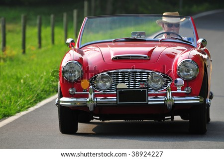 a senior man driving a classic red sports car on a country road