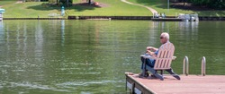 A senior man enjoys fishing on a dock on a peaceful lake on a sunny, summer day.