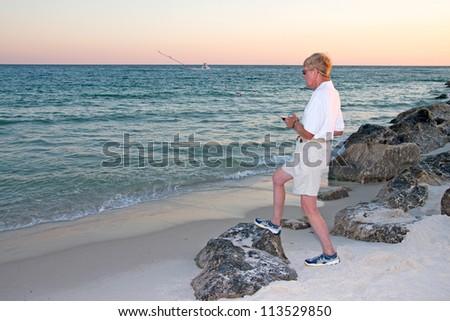 A senior man fishing from the beach on the gulf coast.