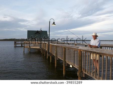 A senior man fishing in the bay at Orange Beach Alabama.