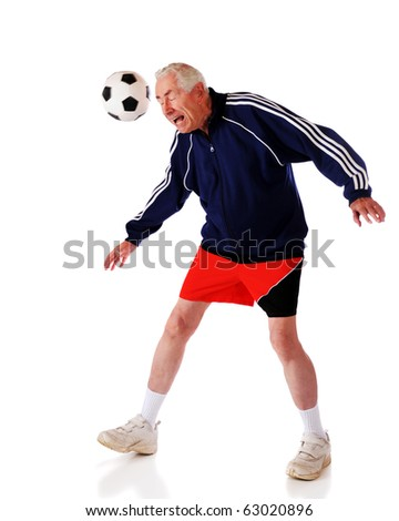 A senior man heading a soccer ball.  Isolated on white.