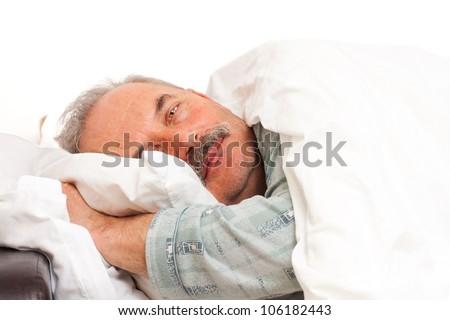 A senior man laying in bad.