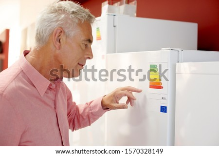 A senior man looking at fridge freezers in an electrical shop
