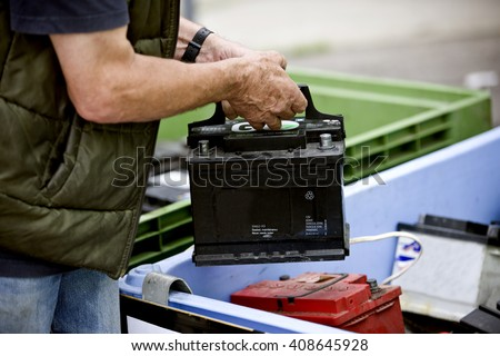A senior man recycling a car battery #408645928