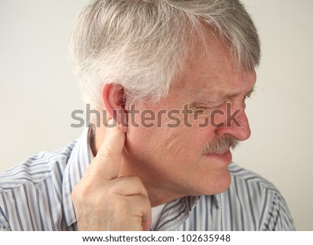 a senior man suffers from pressure behind his ear