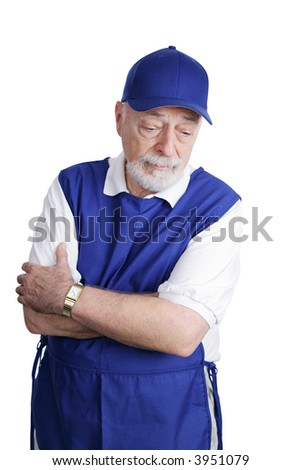 A senior man unable to retire is sad about working a menial service job.  Isolated on white.