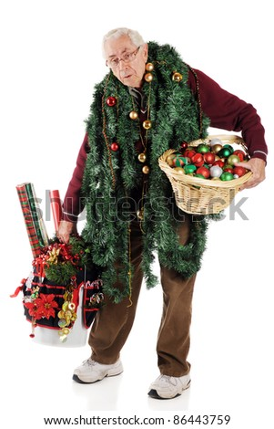 A senior man wearily hauling a bunch of Christmas decor.  On a white background.