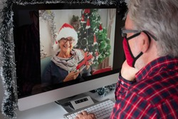 A senior man wearing a mask due to coronavirus on video call for Christmas greetings from home with his wife far away