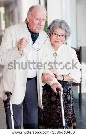 A senior man with a walking frame being assisted by his wife
