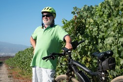 A senior man with white hair and beard standing close to his e bike. Bunches of grapes behind him. Retired elderly caucasian people.Green vineyard in background.