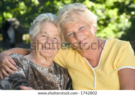 A senior mother sitting by her 60 year old daughter.