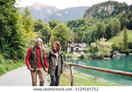 A senior pensioner couple hiking in nature, holding hands.