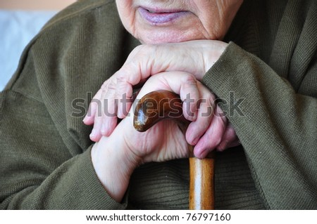 a senior person leaning on a wooden cane