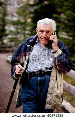 A senior talking on a cell phone outdoors in the forest