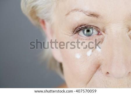 A senior woman applying eye cream