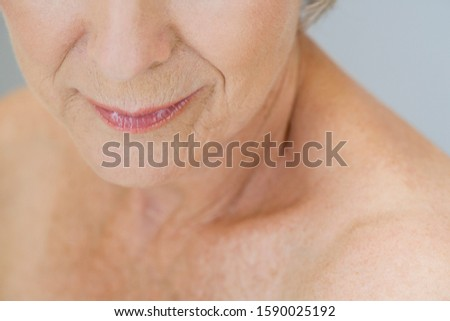 A senior woman, detail of lower half of face and shoulder
