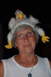 A senior woman having fun wears a silly plush chicken hat on her head