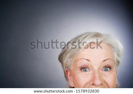 A senior woman looking surprised