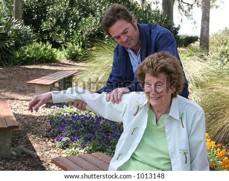 A senior woman receiving physical therapy in the garden.