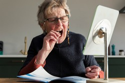 A senior woman takes a mouth sawb at home to check for coronavirus disease