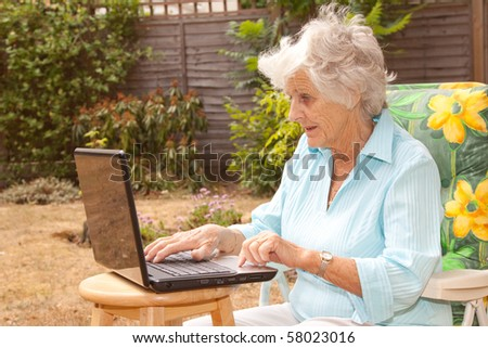 A senior woman using a laptop computer in her garden