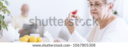 A senior woman wearing glasses looking at a transparent bottle with pills and holding a drug information leaflet. A blurry figure of an older man reading in the background