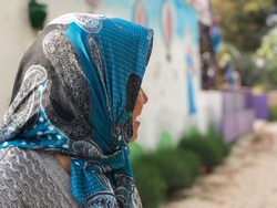 a senior woman with head scarf, looking someting at her back