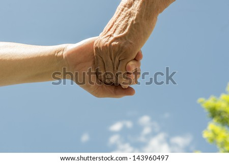 A senior women and daughter holding hands under a blue sky.