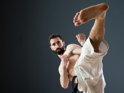 A Sensei karateka instructor trains alone in his dojo; and perform a perfect side kick