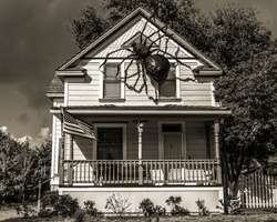 A sepia color image of a spooky house with a spider Halloween decoration climbing on it.