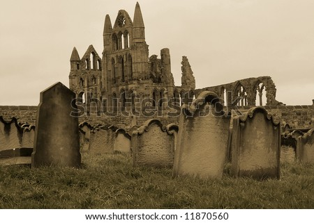 A sepia coloured picture of a graveyard in Whitby, UK, with the ruined abbey in the background