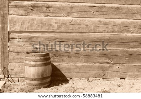 A sepia image of a barrel in front of a worn down building.   The sepia effect conveys an old way of life.  It is intended to be used as a backdrop.