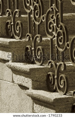 A sepia image of wrought iron handrail and stone steps.