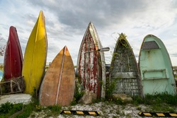 A series of abendoned boats in a parking lot in Maine