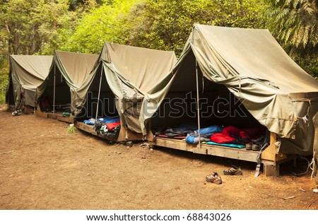A series of basic canvas tents on wooden tent platforms at a Boy Scout camp provide the basics for shelter and not much more. #68843026