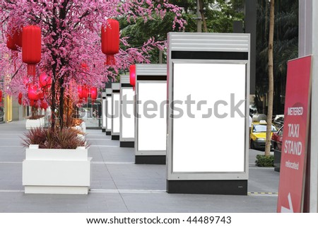 A series of blank signboards on the sidewalk accompanied by beautiful red cherry blossoms with lanterns for Chinese New Year