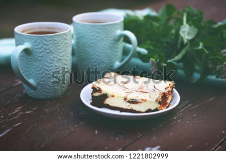 "A series of food pictures. Still life ""In the evening in the garden with a cup of tea and a delicious cheesecake."" The classic still life is made according to all the rules of photography."