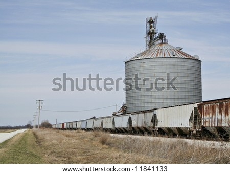 A series of grain cars being loaded with corn at a grain elevator in the midwest