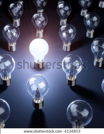 A series of lightbulbs with focus on the one that is bright.