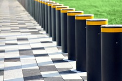 A series of restrictive pillars, fencing on the road. The border between the sidewalk and the lawn with grass.