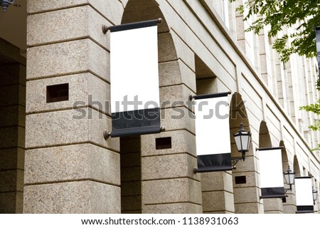 A series of vertical blank advertising mockup of placards are suspended on the facade of the vintage marble  European styled architecture.