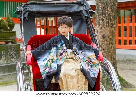 A serious boy dressed in a formal kimono commands a rickshaw at a Japanese shrine; his 7-year-old is here for the 7-5-3 Ceremony, a rite of passage each November 15 #609852296