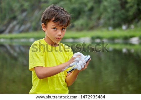 A serious boy is washing a mobile phone with soap while standing in the riverbank. The child ruined  parent's gadget by wetting it .