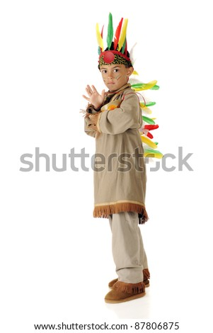 A serious elementary-aged boy beating his drum while wearing an American Indian warrior outfit.  One a white background.